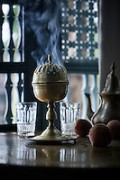 A decorative brass incense burner sits on a table with a coffee pot and figs