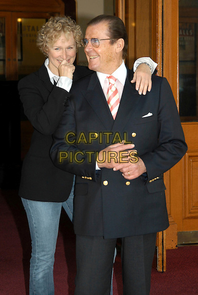 GLENN CLOSE & ROGER MOORE.Photocall for The Night Of 1000 Voices at Royal Albert Hall in aid of the Variety Club Children's Charity, London, UK..May 1st, 2003.half length black blue suit jacket arm over shoulder.CAP/PL.©Phil Loftus/Capital Pictures