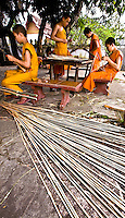 The young monks are making bamboo boats which will be set on fire and floated on the river at night as part of the festival.<br /> (Photo by Matt Considine - Images of Asia Collection)