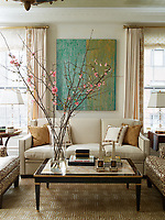 The living room is decorated in neutral tones with the custom-made sofa covered in a Kravet chenille and and the curtains are of a fabric by Coraggio.