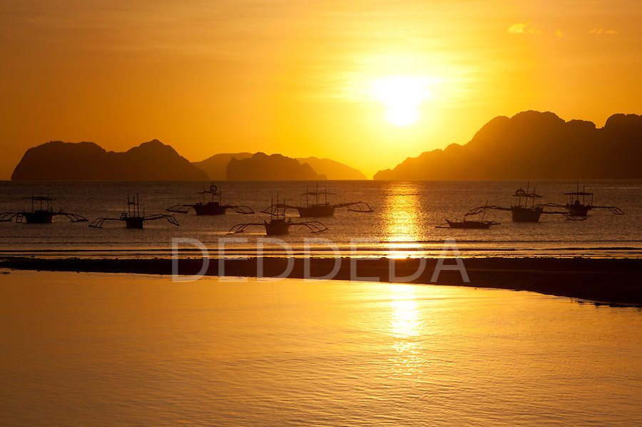 Sunset view of islands and boats from the beaches of Corong Corong near El Nido, Bacuit Archipelago, Philippines.