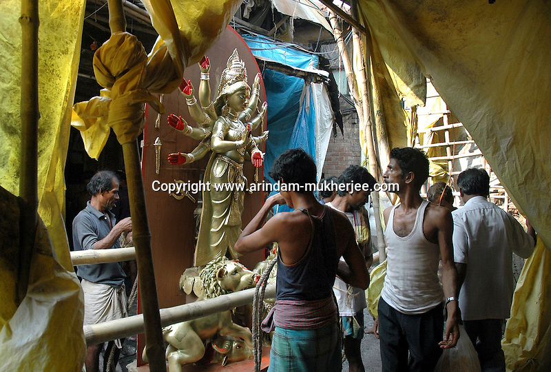 INDIA (West Bengal - Calcutta)  2006, A Durga idol is being prepared to take it to its pandal at a  bylane in Kumortuli. Kumortuli in North Calcutta is the hub of Durga idol makers. During the other time of the year the artists engage themselves in prepairing other idols and masks depending on the assignments. But the most of the earning they aquire from making Durga idols. A Durga idol can cost up to 7000 usd. Which is a big price in Indian Currency.  Durga Puja Festival is the biggest festival among bengalies.  As Calcutta is the capital of West Bengal and cultural hub of  the bengali community Durga puja is held with the maximum pomp and vigour. Ritualistic worship, food, drink, new clothes, visiting friends and relatives places and merryment is a part of it. In this festival the hindus worship a ten handed godess riding on a lion armed wth all possible deadly ancient weapons along with her 4 children (Ganesha - God for sucess, Saraswati - Goddess for arts and education, Laxmi - Goddess of wealth and prosperity, Kartikeya - The god of manly hood and beauty). Durga is symbolised as the women power in Indian Mythology.  In Calcutta people from all the religions enjoy these four days of festival in the moth of October. Now the religious festival has become the biggest cultural extravagenza of Calcutta the cultural capital of India. Artistry and craftsmanship can be seen in different sizes and shapes in form of the idol, the interior decor and as well as the pandals erected on the streets, roads and  parks.- Arindam Mukherjee