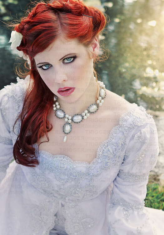 A young woman with red hair wearing a wedding dress and pearls in front of a  pond