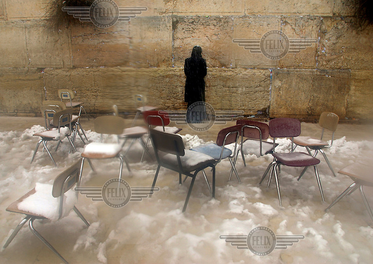 A Jewish woman prays at the Western Wall (Wailing Wall), surrounded by chairs covered in snow, in Jerusalem's Old City after a rare and heavy snow storm.