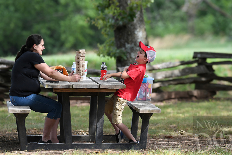 Kaleb Clark, 9, laughs while playing Jenga with his mom Misty Clark of West Fork Sunday June 28, 2020 at Prairie Grove Battlefield State Park. The National Weather Service is calling for a slight chance of rain early this week. Visit nwaonline.com/200628Daily/ for photo galleries. (NWA Democrat-Gazette/J.T. Wampler)