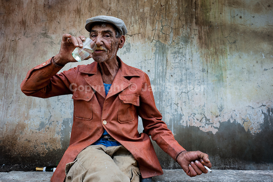 """An old sugar-cane cutter (machetero) drinks rum in front of the apartment block in Bahía, a public housing suburb of Havana, Cuba, 11 February 2011. The Cuban economic transformation (after the revolution in 1959) has changed the housing status in Cuba from a consumer commodity into a social right. In 1970s, to overcome the serious housing shortage, the Cuban state took over the Soviet Union concept of social housing. Using prefabricated panel factories, donated to Cuba by Soviets, huge public housing complexes have risen in the outskirts of Cuban towns. Although these mass housing settlements provided habitation to many families, they often lack infrastructure, culture, shops, services and well-maintained public spaces. Many local residents have no feeling of belonging and inspite of living on a tropical island, they claim to be """"living in Siberia""""."""