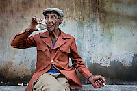 "An old sugar-cane cutter (machetero) drinks rum in front of the apartment block in Bahía, a public housing suburb of Havana, Cuba, 11 February 2011. The Cuban economic transformation (after the revolution in 1959) has changed the housing status in Cuba from a consumer commodity into a social right. In 1970s, to overcome the serious housing shortage, the Cuban state took over the Soviet Union concept of social housing. Using prefabricated panel factories, donated to Cuba by Soviets, huge public housing complexes have risen in the outskirts of Cuban towns. Although these mass housing settlements provided habitation to many families, they often lack infrastructure, culture, shops, services and well-maintained public spaces. Many local residents have no feeling of belonging and inspite of living on a tropical island, they claim to be ""living in Siberia""."
