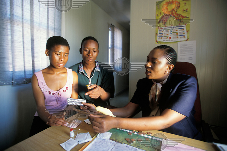 A young couple receiving family planning advice at a clinic. A doctor is explaining the use of the combined contraceptive pill.