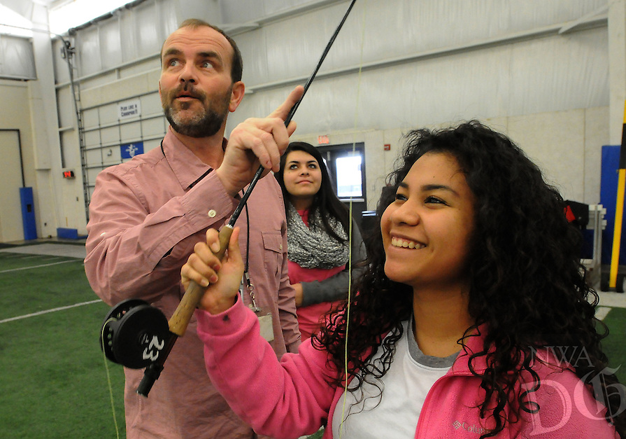 NWA Democrat-Gazette/FLIP PUTTHOFF<br /> FLY CASTING<br /> Jeff Belk, an outdoor education teacher at Rogers High School, helps Estefani Corleto (right) and Stephanie Rodriguez (center) with their technique during a fly casting lesson Tuesday Jan. 19, 2016 at the high school. Outdoor education students are learning to fly fish as part of their preparation for a trout fishing trip to Roaring River State Park near Seligman, Mo., later this semester. Students learn to tie knots, tie flies and study aquatic life as part of the fly fishing unit.