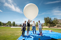 Occidental College physics students Nicole Chen '14 and Jack Nelson '17 build and launch a high-altitude helium balloon carrying a payload of sensors, a video camera and a modified stills camera that will fly to near space. The project was organized by Physics lab supervisor Chuck Oravec. Adjunct assistant professor Rafael Araya-Gochez of the Physics Department also helped. The balloon was launched from Acton, Calif. on May 4, 2014. The balloon, at first thought to be lost, was eventually recovered using the GPS transponder. It was way off course, ending up at Fort Irwin in the Mojave Desert. Due to finals, Nicole and Jack could not be there for the recovery.<br /> (Photo by Marc Campos, Occidental College Photographer)