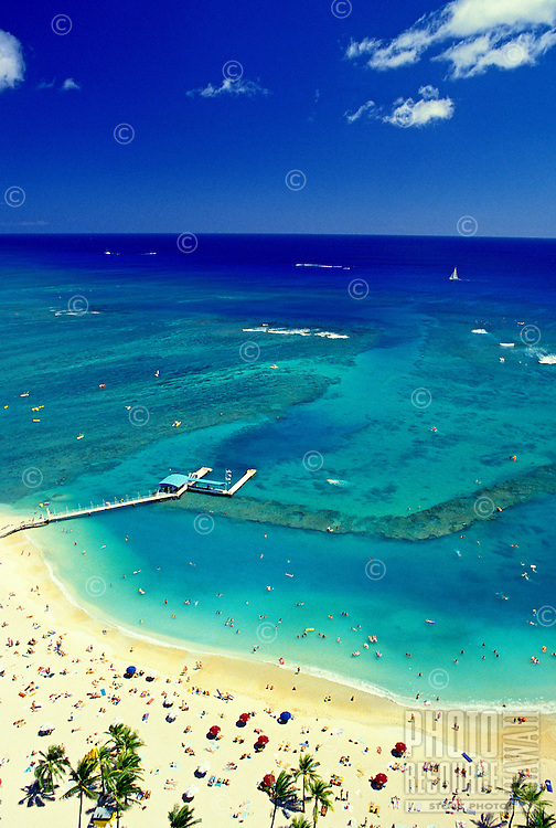 Aerial shot of hundreds of tourists enjoying the white sand beach near the Hilton Hawaiian Village.
