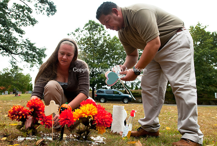 WATERBURY, CT, 28 SEPTEMBER, 2010-092810JS02-Candice Rivera of Wolcott and her husband Jose place decorative items at the grave of their daughter at New Pine Grove Cemetery in Waterbury. Their daughter Katharine Mary Markure died on January 4, 2000.<br />  Jim Shannon Republican-American