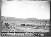 Overall view of Cimarron railroad shops: roundhouse, storehouse, machine shop (in rear) and car shop.  Cimarron town and passenger depot is in distance to the left.  Titled &quot;RR Shops Cimarron, NM&quot;.<br /> St. Louis, Rocky Mountain &amp; Pacific Ry.  Cimarron, NM  Taken by Troutman, Edward A. - ca 1909-1913