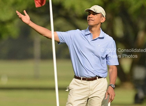 United States President Barack Obama gestures on the 2nd green while golfing at the Marine Corps Base Hawaii's Kaneohe Klipper Golf Course, Kaneohe, Hawaii, January 2, 2014. <br /> Credit: Cory Lum / Pool via CNP