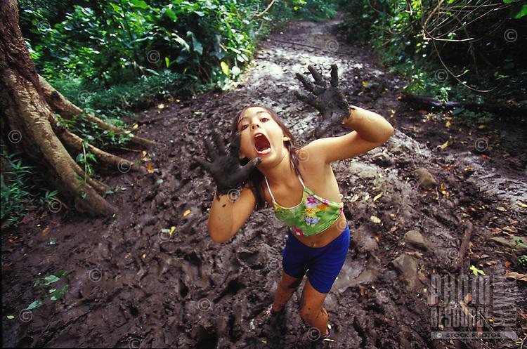 Girl in the mud playing while hiking Maunawili Trail, Kailua, Oahu, Hawaii