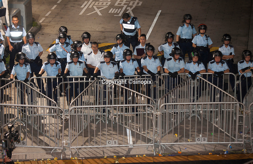 Riot police are seen as student protestors gather at an overnight mass sit-in in front of Hong Kong's Central government offices, Hong Kong, China, 28 September 2014. It was announced at the student protest that the society-wide mass disobedience campaign, Occupy Central would commence immediatley - three whole days earlier than was previously forecast. The students and the Occupy Central supporters are protesting the slow pace of democratic reform imposed by the Chinese government on the Hong Kong people.