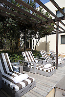 Natural wood weathers to a soft grey in the strong southern Spanish sun softening a terrace deck, its awning and four poolside lounge chairs.