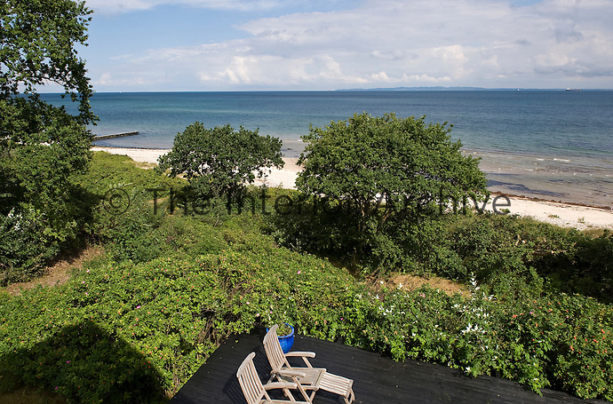 Abundant foliage surrounds the raised terrace separating the property from the beach