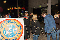 "A number of Occupy Orange County protestors hold the ""Occupy Orange County in unity with Occupy Wall Street"" while marching at South Coast Plaza early in the morning (12:55am).  The Macy's Men's Store is visible in the background.  The protesters were tied together by rope, being led by a single protestor dressed in a suit (as a banker), symbolizing how the 1% lead the 99%."