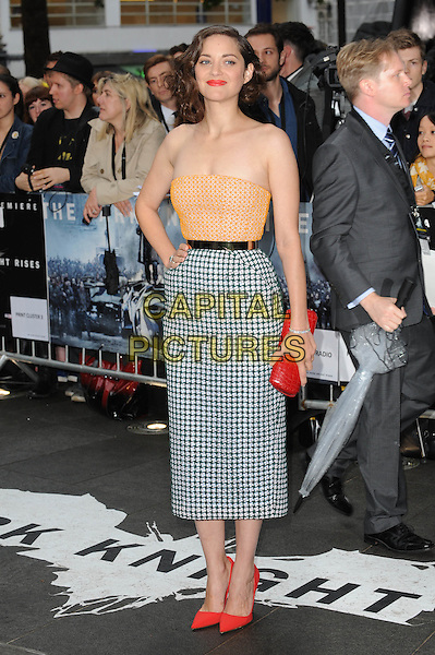 Marion Cotillard (in Christian Dior Couture).'The Dark Knight Rises' European Premiere at The Odeon and Empire cinema, Leicester Square, London, England..18th July 2012.full length orange strapless top hand on hip gold metal waistband white black pattern skirt red clutch bag shoes.CAP/BEL.©Tom Belcher/Capital Pictures.