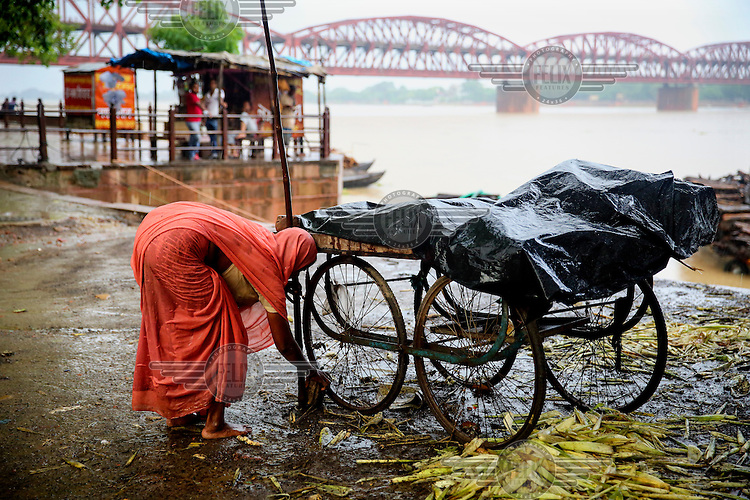 A woman prepares a mobile stall on the banks of the Ganges River. In the background is the Malviya Bridge.