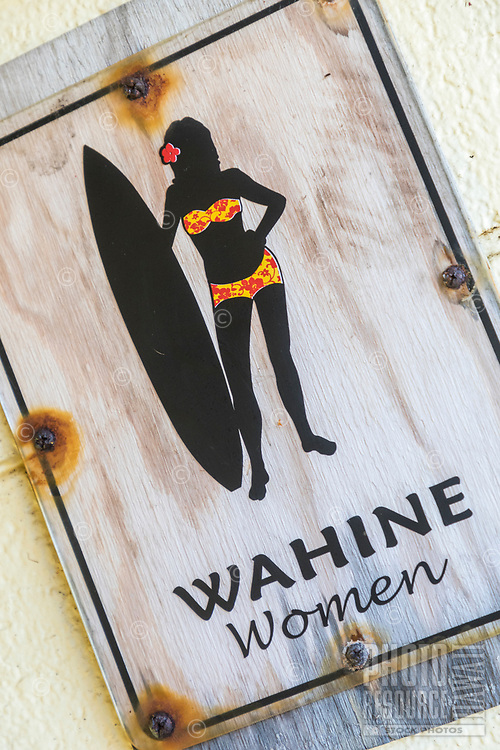 "A weathered ""Wahine Women"" restroom sign at Honoli'i Beach Park, Big Island."