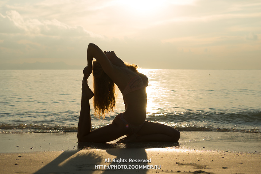 Silhouette of a pigeon pose yoga on the beach