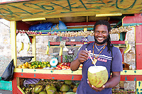 Man selling coconuts from street cart in Falmouth, Jamaica. Jamaica Tourism.