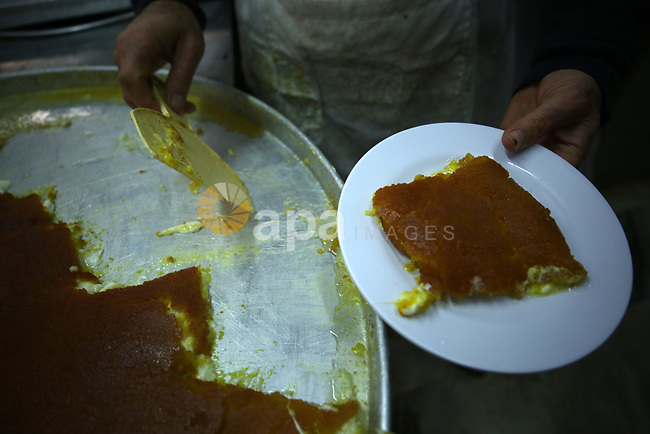 "A Palestinian man prepares a traditional sweets ""Konafa Nabulsi"", in the West Bank city of Nablus, on January 10, 2019. Photo by Shadi Jarar'ah"