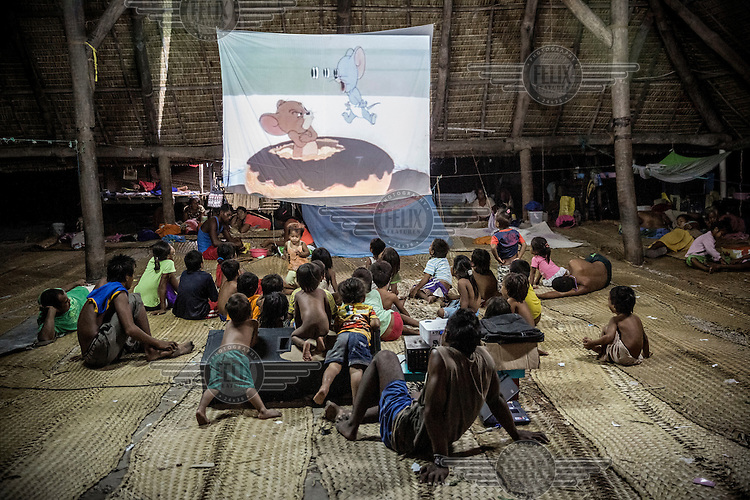 Children watch a screening of a Tom & Jerry cartoon in a 'Maneaba', a traditional I-Kiribati community house.