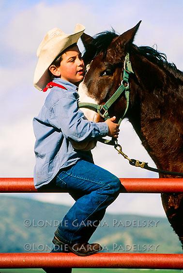 Young cowboy hugs his horse, Central Coast of California