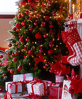 A Christmas tree decorated with red baubles and fairy lights is flanked by matching Christmas stockings and presents
