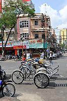 A row of Cyclos (bicycle rickshaws) parked on a busy Ho Chi Minh City (Saigon) street. Vietnam