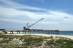 The new pier is being constructed from itself to avoid impacts to the adjacent beach.  The crane on the temporary decking on the pier lifted the pier supports into place ahead of itself.