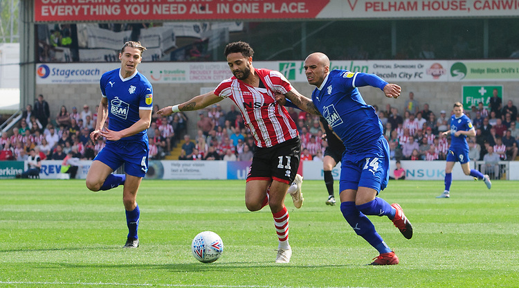 Lincoln City's Bruno Andrade vies for possession with Tranmere Rovers' Jake Caprice<br /> <br /> Photographer Chris Vaughan/CameraSport<br /> <br /> The EFL Sky Bet League Two - Lincoln City v Tranmere Rovers - Monday 22nd April 2019 - Sincil Bank - Lincoln<br /> <br /> World Copyright © 2019 CameraSport. All rights reserved. 43 Linden Ave. Countesthorpe. Leicester. England. LE8 5PG - Tel: +44 (0) 116 277 4147 - admin@camerasport.com - www.camerasport.com