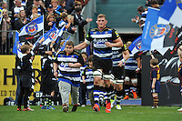 Stuart Hooper of Bath Rugby, mascot in hand, leads his team out onto the field. West Country Challenge Cup match, between Bath Rugby and Exeter Chiefs on October 10, 2015 at the Recreation Ground in Bath, England. Photo by: Patrick Khachfe / Onside Images