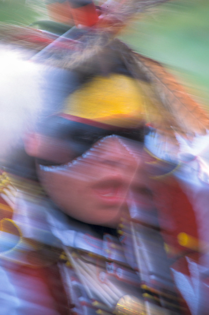 Motion blur of a Blackfeet dance participant in traditional  regalia and face paint during the annual Pow wow at the Blackfeet Indian Days Festival in Browning Montana