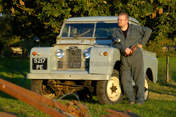 Workman in overall leaning  against a historic 1963 Landrover Series 2a truckcab in very original and full working condition on a farm in Dunsfold, UK 2004. --- RELEASES AVAILABLE FOR CERTAIN USES. Automotive trademarks are the property of the trademark holder, authorization may be needed for some uses.