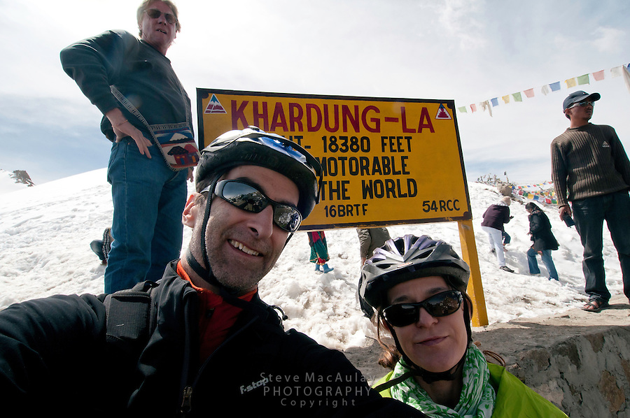 Self portrait of two mountain bikers at Khardung La at 18,380ft. the summit of the highest motorable road in the world.  Himalayan Mountains, Ladakh, India.
