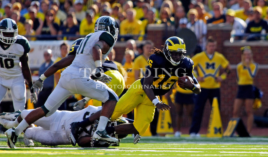 Michigan quarterback Denard Robinson (16) is tripped up on a carry in the second quarter of an NCAA college football game with Michigan State, Saturday, Oct. 9, 2010, in Ann Arbor, Mich. (AP Photo/Tony Ding)