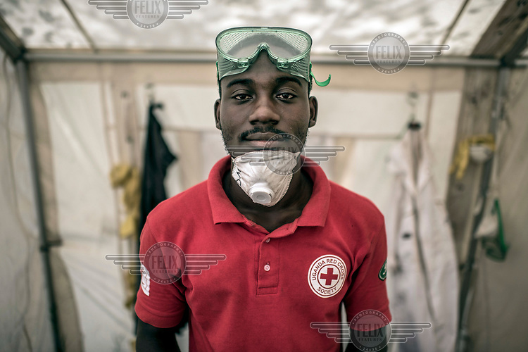 Agaba Derrick, a 24 year old volunteer laboratory assistant for the Red Cross, in a water treatment plant.