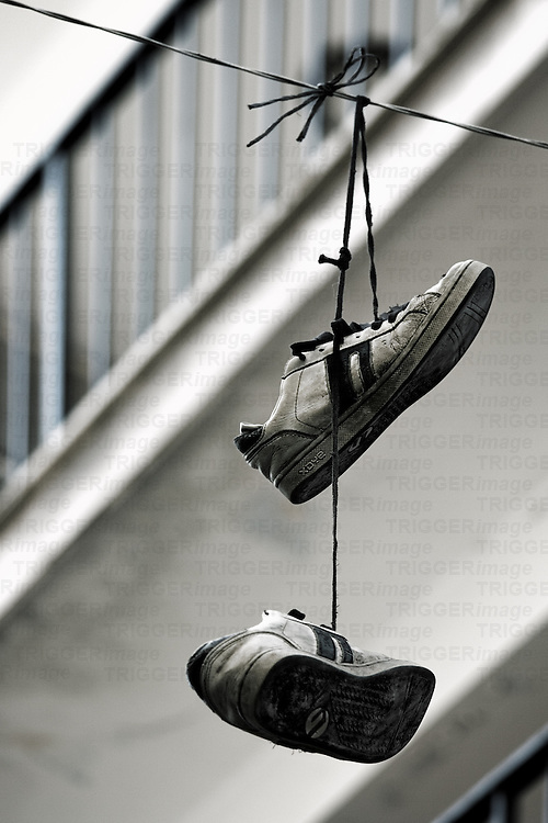 A pair of training shoes hanging on a line