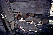 Rio de Janeiro, Brazil. Favela shanty town; two small children behind a barrier.