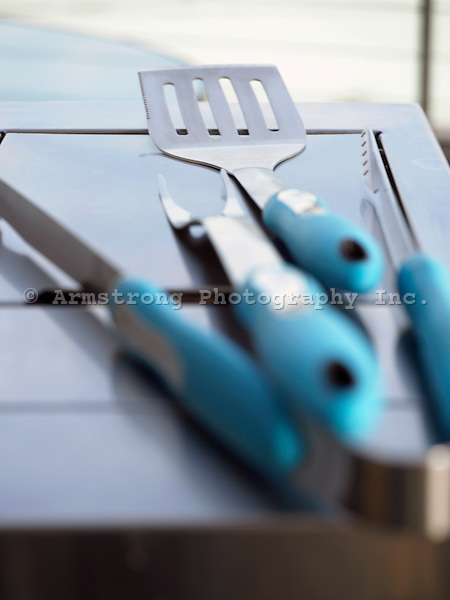 Various tools for grilling food on a stainless steel surface.