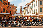 Motorbikes and outdoor cafes with Piazza Erbe and Lamberti Tower in the background