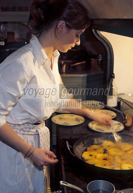 France/84 Vaucluse/Avignon: Table d'Hote de la Mirande dans la cuisine médiévale d'un ancien palais de Cardinal- Aurore prépare l'ananas roti au miel sur le fourneau à bois