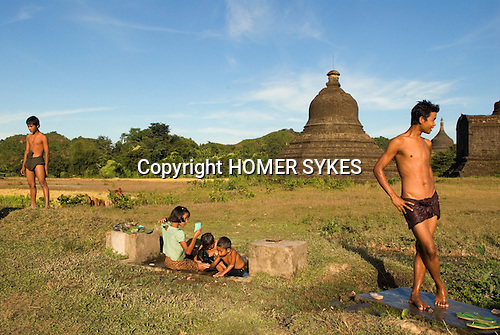 Mrauk U Myanmar (Burma) 2008. Young men washing late afternoon in background Lay Mye Thna Temple.<br />