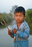 Heab Hear, 4, fishes at sunrise in the village of Dong in northern Cambodia.