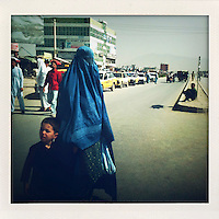 A burqa clad woman walking with a boy cross a Kabul street.