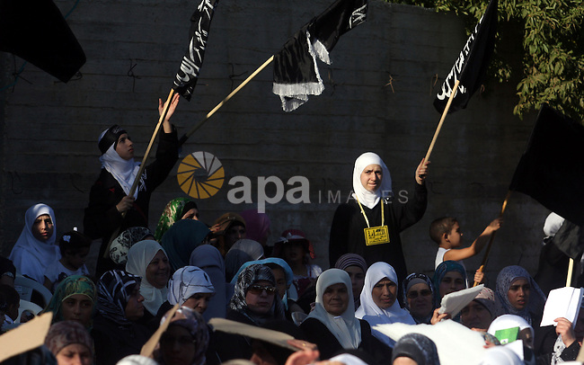 """Palestinian supporters of Hizb ut-Tahrir or the Islamic Liberation Party, chant slogans and wave black and white flags with the religous writing """"There is no God but God, and Mohammed is his prophet"""" during a rally in the West Bank city of Ramallah, on July 7, 2012. The Islamic Liberation Party, which calls for the return of the Islamic caliphate and the establishment of an Islamic states, has no military power in the Palestinian territories and its goal is to join all Muslim countries under one nation. Photo by Issam Rimawi"""